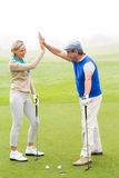 Golfing couple high fiving on the golf course. On a foggy day at the golf course Royalty Free Stock Photo
