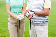 Golfing couple holding clubs Stock Photo