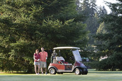 Golfing Couple - Horizontal. A happy couple standing near their golf cart smiling with their arms around each other. Horizontally framed photo Stock Photos