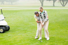 Golfing couple putting ball together. On a foggy day at the golf course stock images