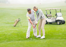 Golfing couple putting ball together Royalty Free Stock Photo