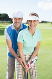 Golfing couple putting ball together smiling at camera Stock Photos