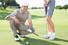Golfing couple on the putting green with man smiling at camera Stock Photos