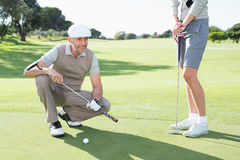 Golfing couple on the putting green Royalty Free Stock Image