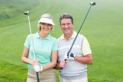 Golfing couple smiling at camera holding clubs. On a foggy day at the golf course royalty free stock photo