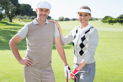 Golfing couple smiling at camera and holding clubs Stock Photography