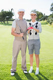 Golfing couple smiling at camera holding clubs Stock Image