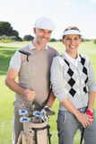 Golfing couple smiling at camera on the putting green Stock Photos
