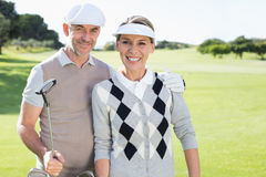 Golfing couple smiling at camera on the putting green. On a sunny day at the golf course royalty free stock image