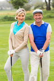 Golfing couple smiling at camera on the putting green Royalty Free Stock Photography