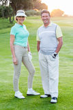 Golfing couple smiling at camera on the putting green Royalty Free Stock Photo