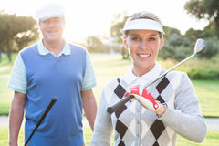 Golfing couple smiling at camera Royalty Free Stock Image