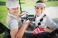 Golfing couple smiling at camera in their golf buggy Stock Images