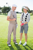 Golfing couple smiling at each other holding clubs Stock Image