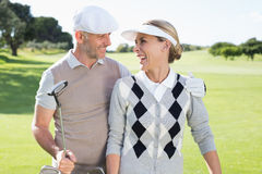 Golfing couple smiling at each other on the putting green Royalty Free Stock Photos