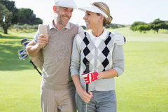 Golfing couple smiling at each other on the putting green Royalty Free Stock Images