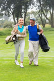 Golfing couple smiling at each other on the putting green Royalty Free Stock Photo