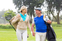 Golfing couple smiling at each other on the putting green Royalty Free Stock Photography