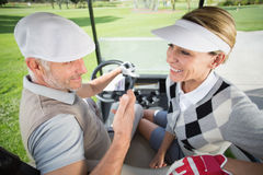 Golfing couple smiling at each other in their golf buggy Royalty Free Stock Images