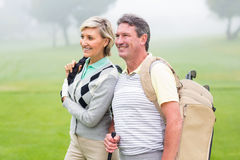Golfing couple smiling and holding clubs Royalty Free Stock Photos