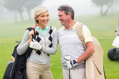 Golfing couple smiling and holding clubs. On a foggy day at the golf course royalty free stock image