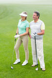 Golfing couple smiling and holding clubs Stock Photo