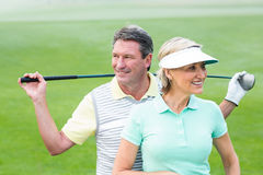 Golfing couple smiling and holding clubs Royalty Free Stock Image