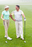 Golfing couple smiling and holding clubs. On a foggy day at the golf course stock image