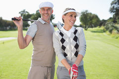 Golfing couple smiling and holding clubs Stock Photos