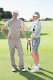 Golfing couple smiling and holding clubs Stock Images
