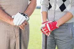 Golfing couple standing and holding clubs Royalty Free Stock Photos