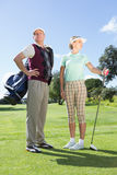 Golfing couple standing and looking around Stock Image