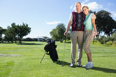 Golfing couple standing smiling at camera. On a sunny day at the golf course stock images