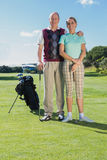 Golfing couple standing smiling at camera Stock Photo