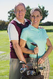 Golfing couple standing smiling at camera Stock Photos