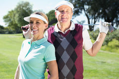 Golfing couple standing smiling at camera Royalty Free Stock Images