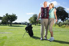 Golfing couple standing smiling at each other Royalty Free Stock Image