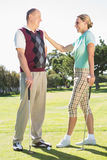 Golfing couple standing smiling at each other Stock Photography