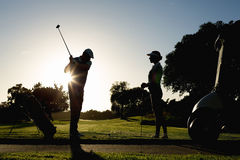 Golfing couple teeing off for the day. On a sunny morning at the golf course royalty free stock images