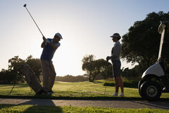 Golfing couple teeing off for the day. On a sunny morning at the golf course stock photo