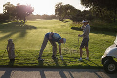 Golfing couple teeing off for the day Stock Photography