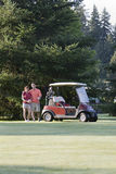 Golfing Couple - Vertical. A happy couple standing near their golf cart smiling with their arms around eachother. Vertically framed photo royalty free stock photos