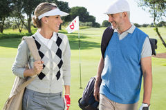 Golfing couple walking away from eighteenth hole Royalty Free Stock Image