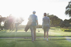 Golfing couple walking and chatting Stock Image