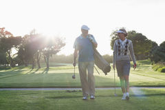Golfing couple walking and chatting Royalty Free Stock Image