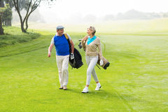 Golfing couple walking on the putting green. On a foggy day at the golf course royalty free stock images