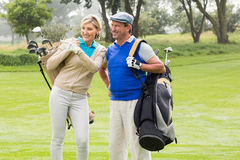 Golfing couple walking on the putting green Royalty Free Stock Image