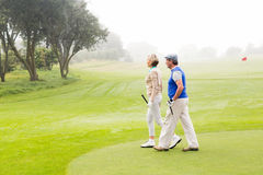 Golfing couple walking on the putting green Royalty Free Stock Photos