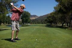 Golfing do homem foto de stock