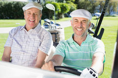 Golfing friends driving in their golf buggy smiling at camera Royalty Free Stock Image